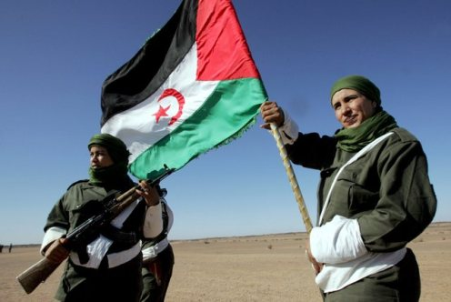Sahrawi woman soldier carries a flag of the Democratic Arab Republic of Sahara during a parade
