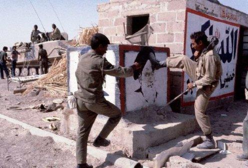 1980, cerca de Abadan, Irak---soldados iraquíes retirar un cartel del Ayatollah