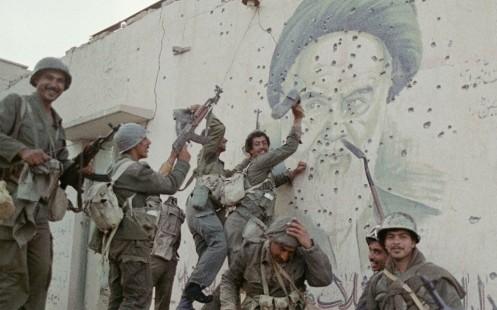 soldados iraquíes posan frente a un mural acribillado de líder iraní Ayatollah Khomeini, 20 de abril de 1988 - copia